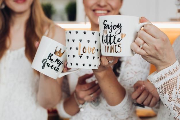 Mama, papa en dochter ontbijten samen met kopjes thee of koffie en verheugen zich