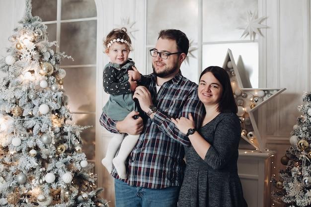 Mama, papa en hun kleine kind in kerstsfeer