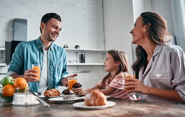 Mama, papa en hun kleine mooie dochter ontbijten in de keuken en praten. gelukkig gezin concept.