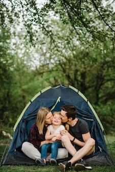 Mama, papa kussen en knuffelen een kind en genieten van een kampeervakantie op het platteland