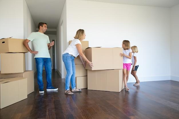 Mama, papa, twee meisjes die dozen dragen en stapel maken in hun nieuwe lege flat