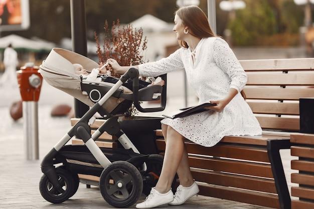 Mama zittend op een bankje. vrouw duwt haar peuterzitting in een kinderwagen. dame met een tablet.