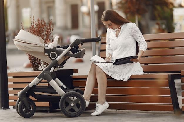 Mama zittend op een bankje. vrouw duwt haar peuterzitting in een kinderwagen. dame met een tablet