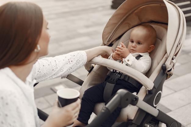 Mama zittend op een bankje. vrouw duwt haar peuterzitting in een kinderwagen. familie concept.