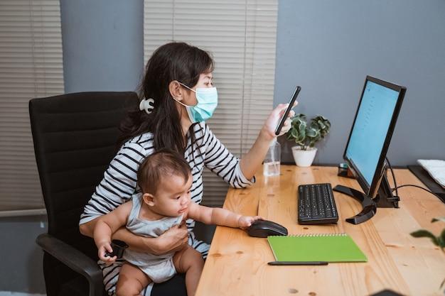 Mamma die maskers dragen die haar baby dragen die naar huis werken