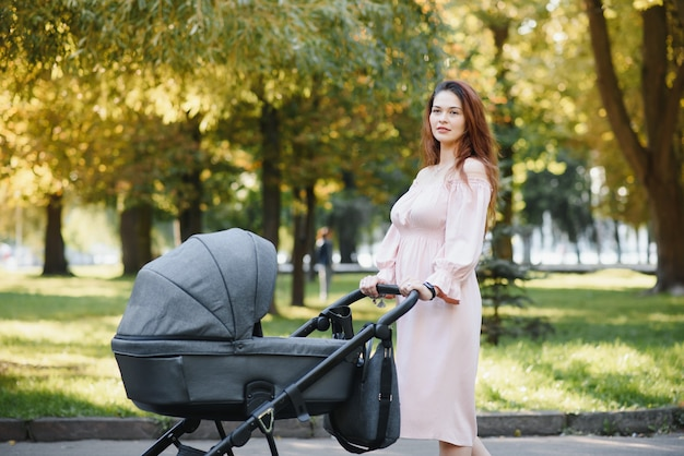Mamma die op stadsstraat lopen. vrouw duwt haar peuter zittend in een kinderwagen. familieconcept.