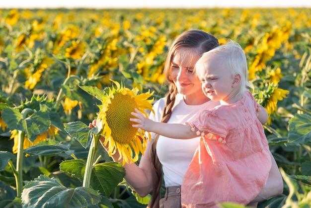 Mamma en baby lopen in zonnebloemgebied