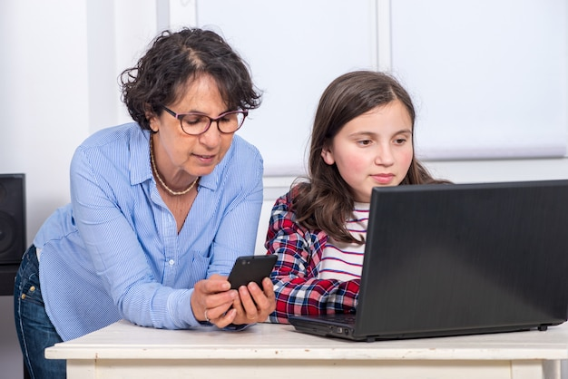 Mamma en dochter die laptop thuis met behulp van