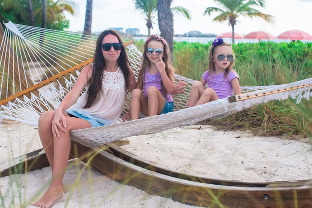 Mamma en kleine meisjes die in hangmat bij tropische toevlucht ontspannen
