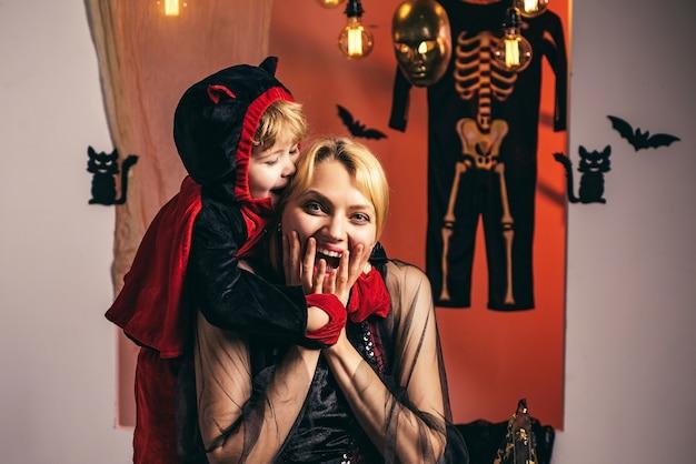 Mamma en weinig kindjongen dichtbij pompoen en halloween-decoratie