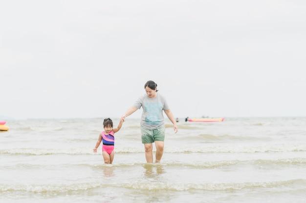Mamma met dochter die in het overzees loopt en handen houdt