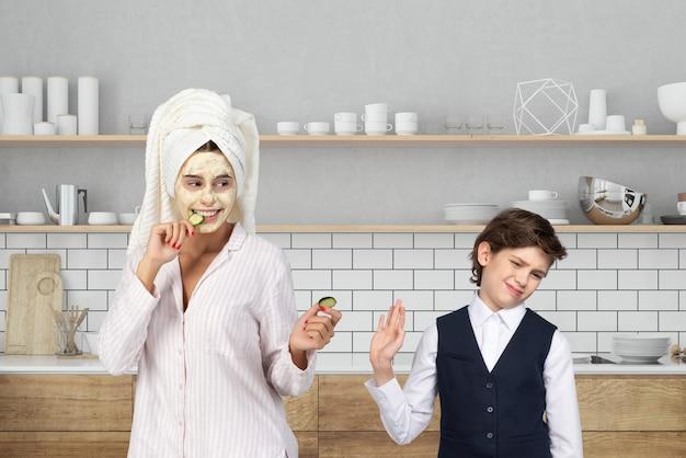 Mamma met gezichtsmasker en haar dat in handdoek wordt verpakt stelt komkommerplak voor om aan haar zoon te eten
