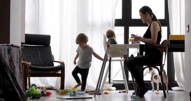 Mamma met haar twee kinderen die thuis zitten. een ouder voedt een kind in een hoge stoel.