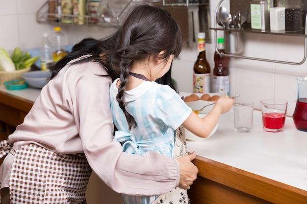 Mamma met manu van het kind kokende ei in de keuken aan moedersdag, toevallige levensstijl.