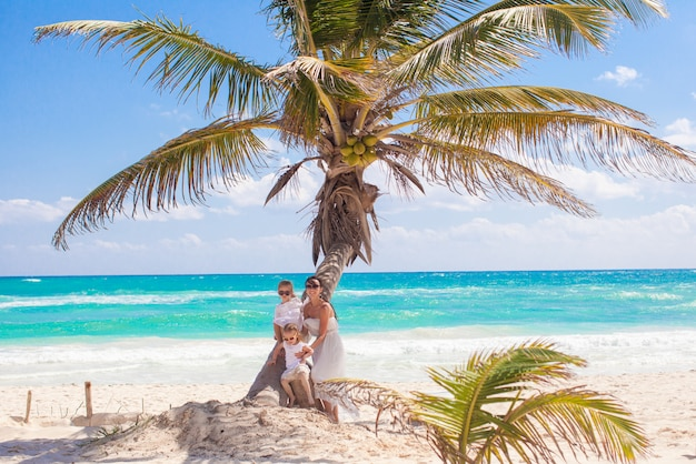 Mamma met twee dochters op een palm die van vakanties geniet bij het strand