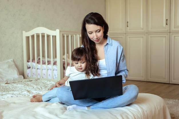 Mamma op moederschapsonderneemster die aan laptop bij freelance verre het werkzitting op bed werken. naast haar is haar dochtertje.