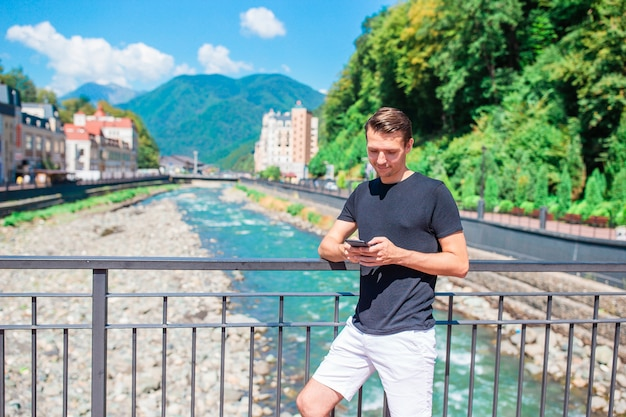 Man aan de kade van een bergrivier in een europese stad.