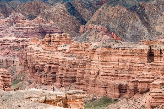 Man aan de rand van rode zandsteen canyon