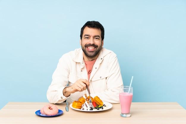 Man aan een tafel met ontbijt wafels en een milkshake