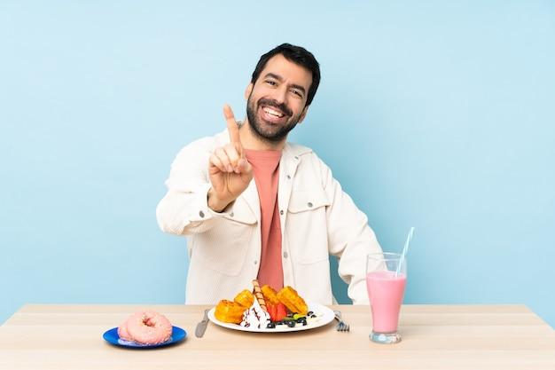 Man aan een tafel met ontbijtwafels en een milkshake die een vinger toont en opheft