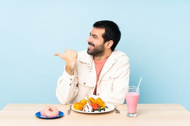 Man aan een tafel met ontbijtwafels en een milkshake die naar de zijkant wijst