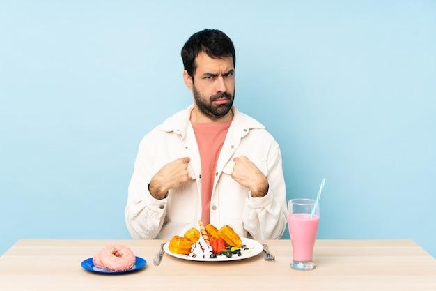 Man aan een tafel met ontbijtwafels en een milkshake die naar zichzelf wijst