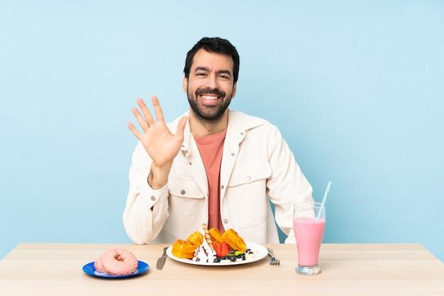 Man aan een tafel met ontbijtwafels en een milkshake die vijf telt met vingers