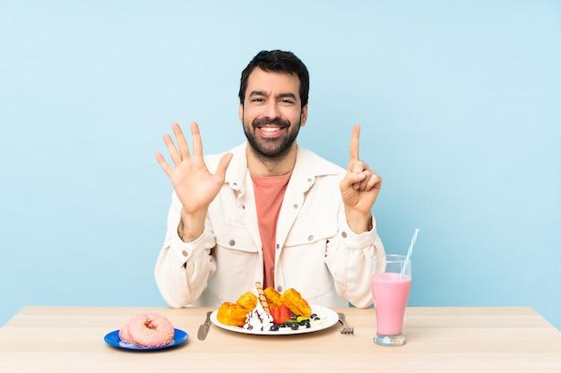 Man aan een tafel met ontbijtwafels en een milkshake die zes met vingers telt