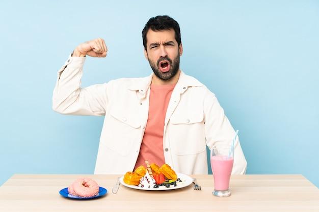 Man aan een tafel met ontbijtwafels en een milkshake doet sterk gebaar