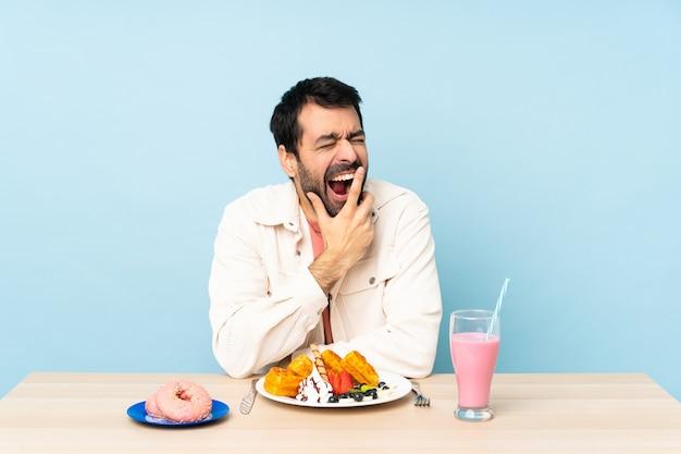 Man aan een tafel met ontbijtwafels en een milkshake geeuwen