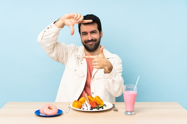 Man aan een tafel met ontbijtwafels en een milkshake gericht gezicht. framing symbool