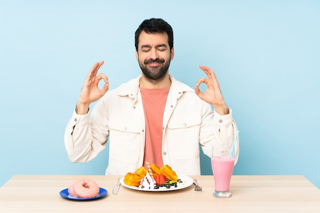Man aan een tafel met ontbijtwafels en een milkshake in zen pose