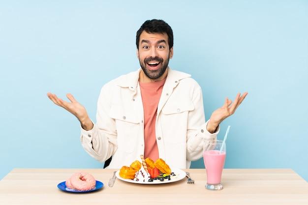Man aan een tafel met ontbijtwafels en een milkshake met geschokte gelaatsuitdrukking