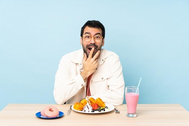 Man aan een tafel met ontbijtwafels en een milkshake met glazen en verrast