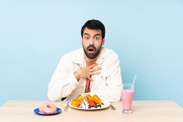 Man aan een tafel met ontbijtwafels en een milkshake verrast en geschokt terwijl hij er goed uitzag