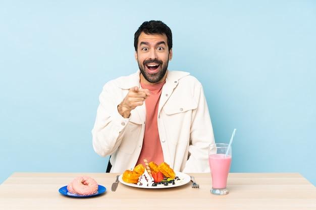 Man aan een tafel met ontbijtwafels en een milkshake verrast
