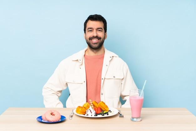 Man aan een tafel met ontbijtwafels en een milkshake