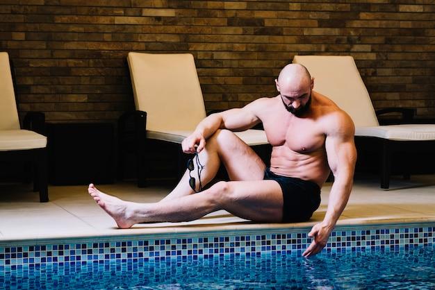 Man aan het raken van zwembad water