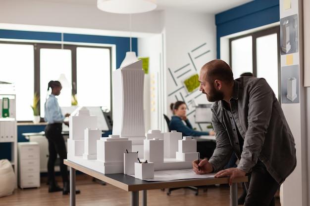 Man aan het werk aan architectonisch ontwerp op kantoor