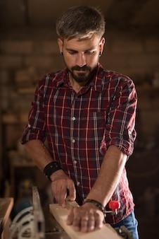 Man aan het werk als timmerman in zijn eigen atelier houtbewerking