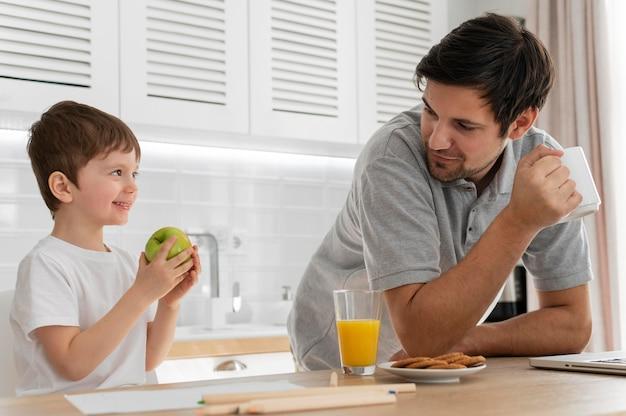 Man aan het werk bij bureau met zoon