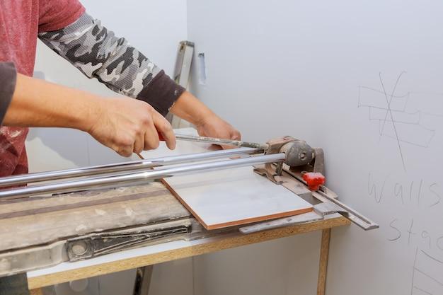 Man aan het werk bij de cut de ceramiektegel op de handmatige tegelsnijden