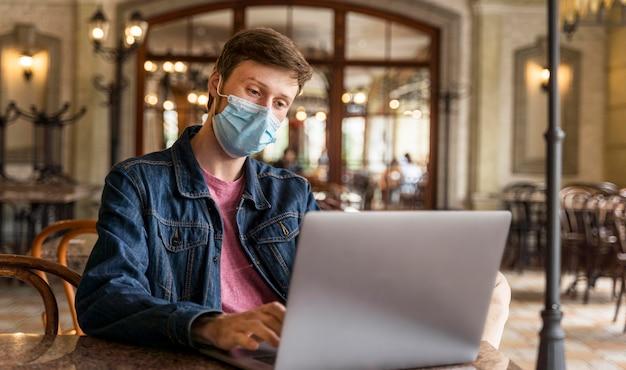 Man aan het werk binnenshuis terwijl het dragen van een gezichtsmasker