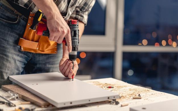 Man aan het werk die gaten in het bord maakt met boor tijdens het proces van meubelproductie