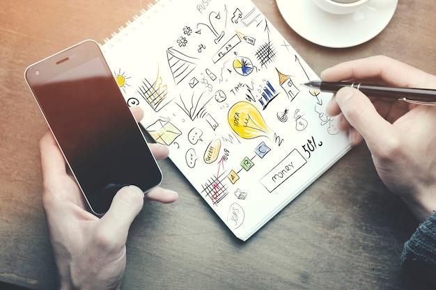 Man aan het werk - hand pen en telefoon, kopje koffie op houten tafel