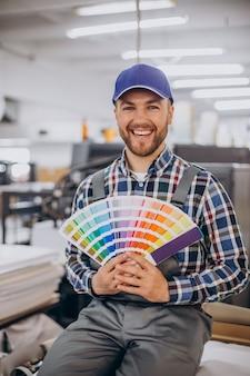 Man aan het werk in de drukkerij met papier en verf Premium Foto
