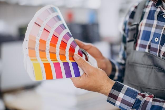 Man aan het werk in de drukkerij met papier en verf