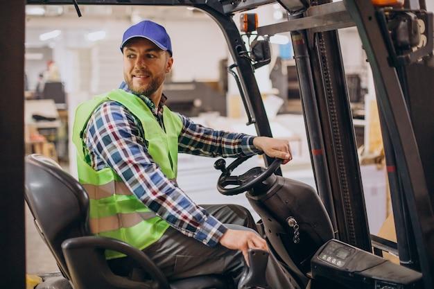 Man aan het werk in het magazijn en heftruck rijden