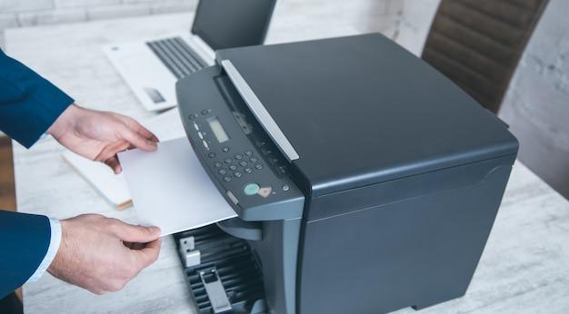 Man aan het werk in xerox-apparaat op kantoor