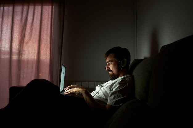 Man aan het werk laat thuis. hij zit in het donker op de bank.